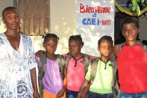 Parents et jeunes du CAEJ-Haïti avec leurs effets scolaires