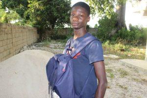 Jeune du CAEJ-Haïti avec ses effets scolaires